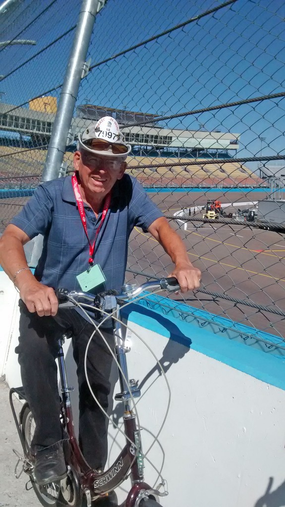Jim on fold-up bicycle overlooking speedway