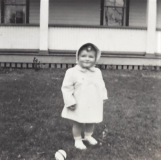 A very young me in front of our family home